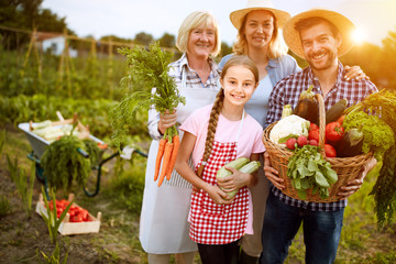 Rural family satisfied with vegetables products from garden