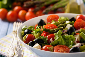 Vegetable salad with asparagus, tomatoes, feta cheese and olives.