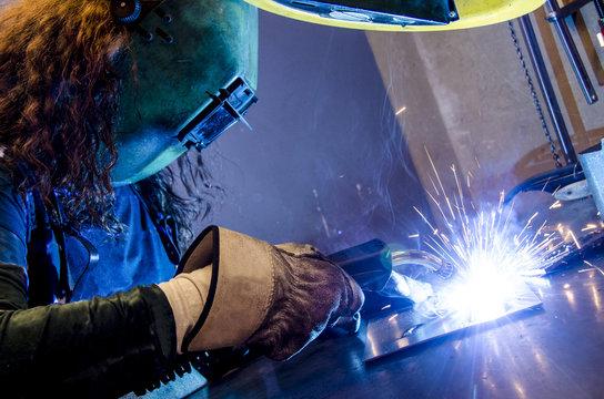 Woman welding in the metal industry