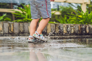 Little boy runs through a puddle. summer outdoor