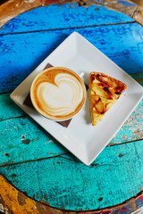 Cappuccino coffee and apple pie on colorful green and blue cafe table