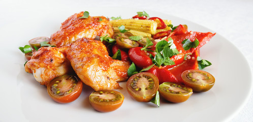 roasted chicken wings with vegetables sprinkled with parsley
