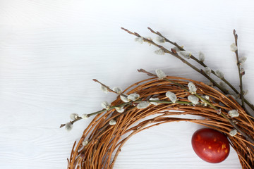 festive Easter decoration/ Wreath of twigs with willow branches and egg on a light wooden surface