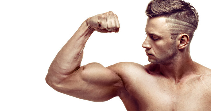 muscular super-high level handsome man posing on white background. showing his biceps.