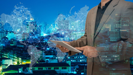 Double exposure of business man using tablet with cityscape background