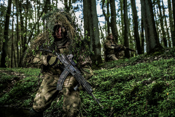 Camouflaged soldier in forest