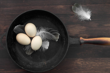 Three raw chicken eggs in a black cast-iron frying pan