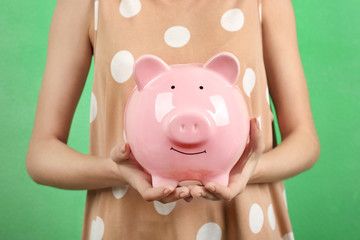 Young woman with piggy bank on color background, closeup