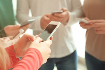 People standing together and using smartphones, closeup