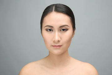 Portrait of beautiful Asian woman on gray background