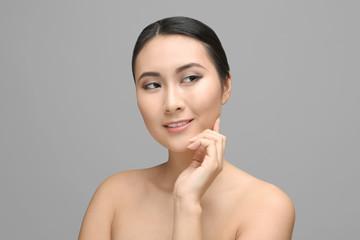 Portrait of beautiful Asian woman on gray background