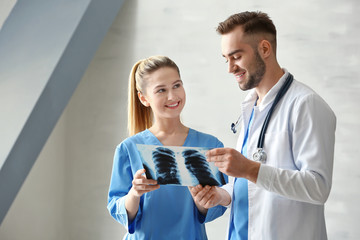 Doctor and medical assistant discussing x-ray image in office