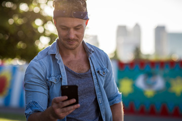 Young adult walking down street using smartphone