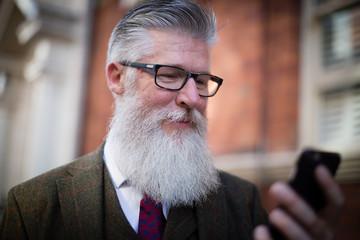 Senior male walking down street using smartphone