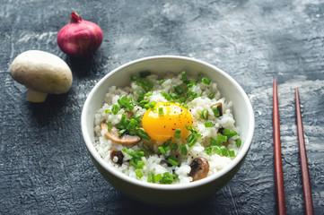 Traditional asian food (Tamago kake gohan) - hot white rice with mushrooms, raw yolk and green onion.
