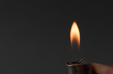 Hand igniting fire with lighter on dark background