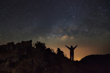 Milky way galaxy and silhouette of a standing happy man at Doi Luang Chiang Dao with Thai Language top point signs. Long exposure photograph.With grain
