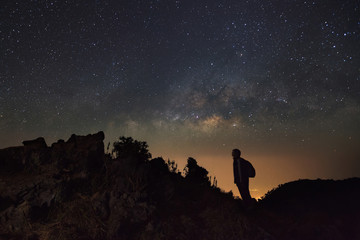 Landscape with milky way, Night sky with stars and silhouette of a standing man at Doi Luang Chiang Dao with Thai Language top point signs. Long exposure photograph.With grain