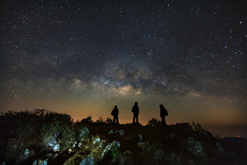 Landscape with milky way, Night sky with stars and silhouette of a standing man on Doi Luang Chiang Dao mountain, Long exposure photograph, with grain