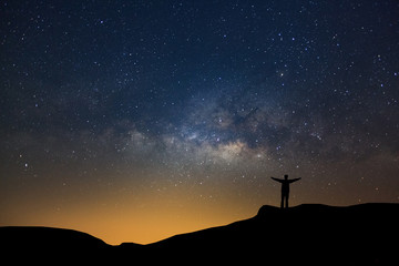 Landscape with milky way, Night sky with stars and silhouette of happy people standing on the mountain, Long exposure photograph, with grain