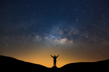 Milky way galaxy with stars and silhouette of a standing happy man, Long exposure photograph, with grain.