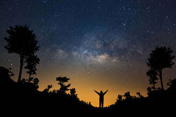 Milky way galaxy and silhouette of a standing happy man in forest, Long exposure photograph, with grain.