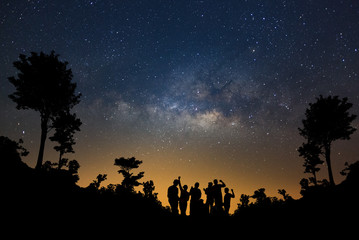 Landscape with milky way, Night sky with stars and silhouette of happy people standing in forest, Long exposure photograph, with grain.