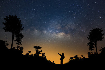 A Man is standing next to the milky way galaxy pointing on a bright star in forest, Long exposure photograph, with grain.