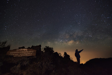 Doi Luang Chiang Dao, Chiang Mai - Febuary 13, 2016 : A Man is standing next to the milky way galaxy pointing on a bright star at Doi Luang Chiang Dao High moutain top point signs.