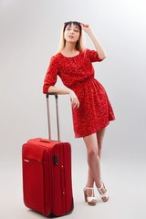 Portrait of pretty woman in red with travel bag. Female model isolated studio background.