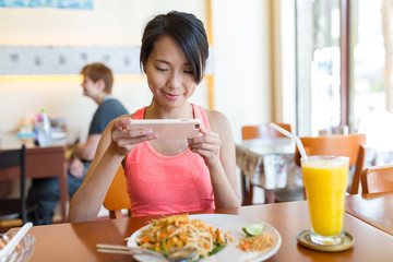 Woman taking photo on dishes in restaurant