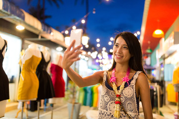 Woman visiting night market and taking selfie by mobile phone