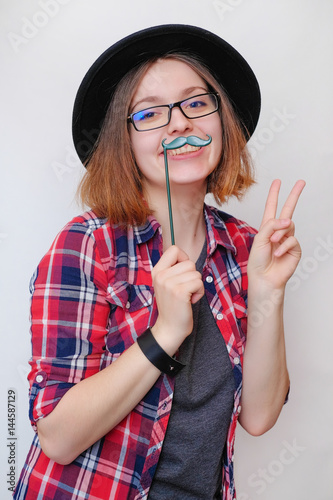 c9a7296ee9d0d9 Girl having fun in red plaid shirt, jeans, black hat. Hipster girl style  posing, smiling, do fake mustache on a white background. Look into the  camera.