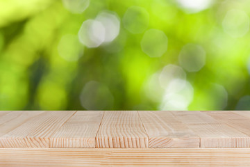 Wood table top on natural green bokeh background- can be used for montage or display your products