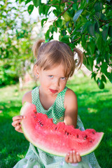 e78026503318 Little girl in green dress, barefoot standing in the park with big ...