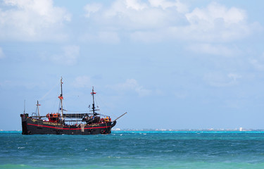 Pirate ship sailing in the Caribbean sea. The boat composed to the left.