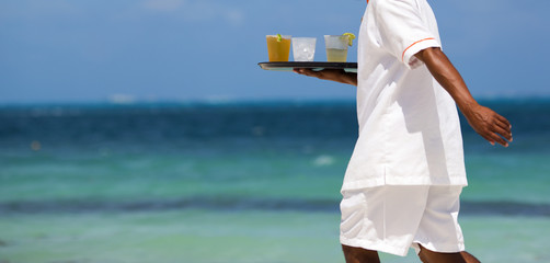 Waiter carrying drinks on the beach. Turquoise sea in the background.