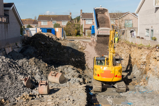 Excavator is digging a house foundation in a residential area while a dumper truck is unloading construction gravel, sand and crushed stones on the construction site.