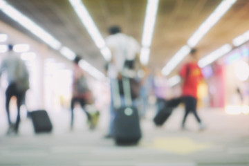 blur background of terminal departure with passengers in an airport