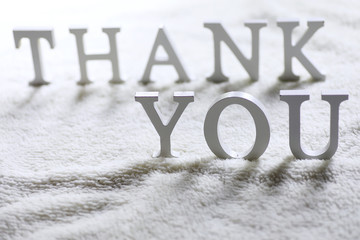 Wooden wthite letter Thank you on the crumpled carpet