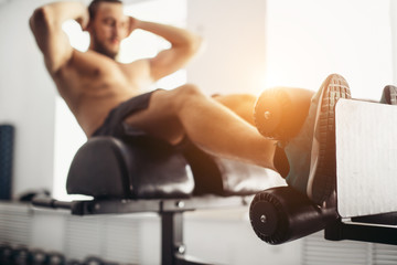 Muscular man exercising doing sit up exercise. Athlete with six pack, white male, no shirt. shallow focus