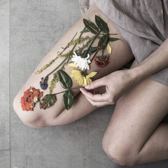 Woman arranging dried flattened flowers on her leg
