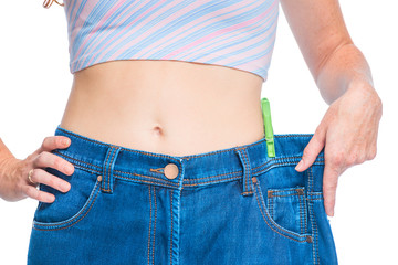 The result of an effective diet, a slim figure in large jeans closeup