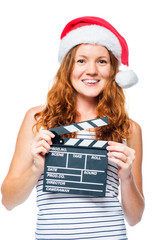 Beautiful girl in a santa hat with a movie clapper on a white background