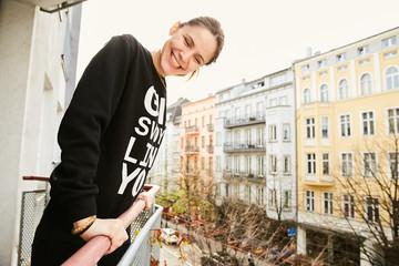 A girl on a balcony in berlin having fun