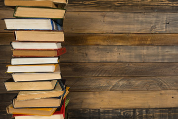 Books in a stack in left side with the grunge wooden table background.