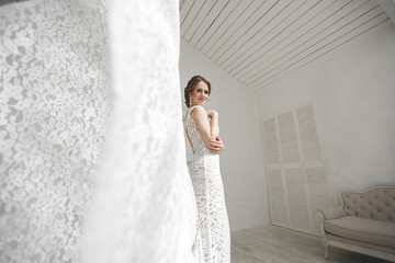 Beautiful bride posing in wedding dress in a white photo Studio. Mirror. Sofa. Bouquet. The door. Chandelier.