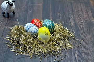 Easter eggs deposited in the hay on the wooden board.