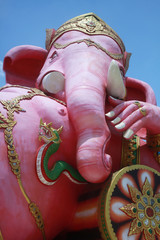 close-up ancient carving of clining peace Ganesha god, god of successful with blue clear sky background
