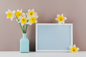 Mockup of picture frame decorated narcissus flowers in vase with empty space for text your blogging and greeting for mother day.